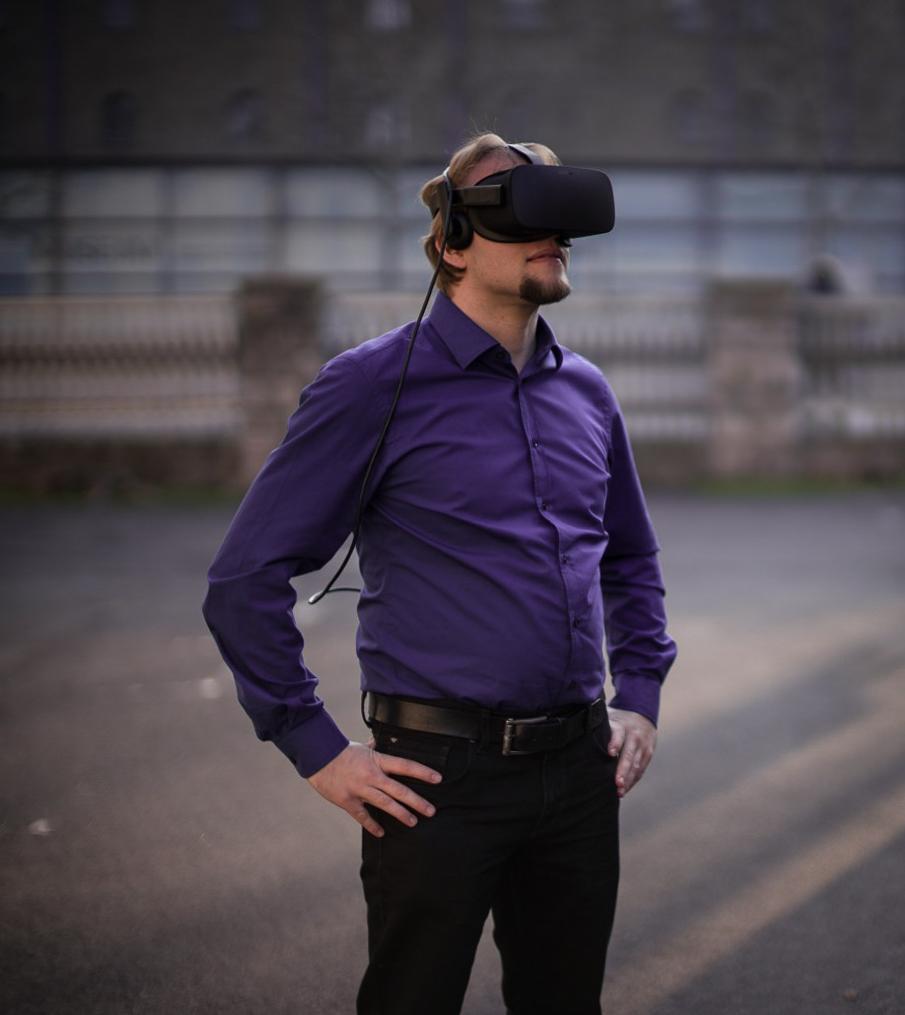 Mann steht mit AR-VR-Brille in einer industriellen Umgebung